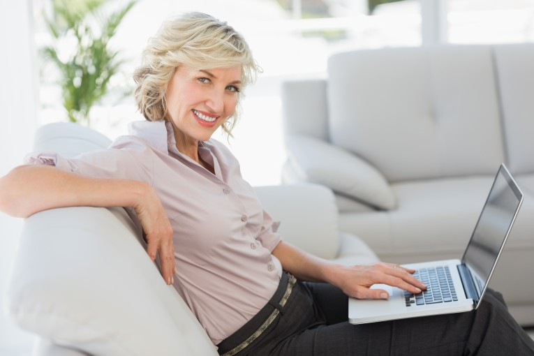 Side view portrait of beautiful businesswoman using laptop in the living room at home